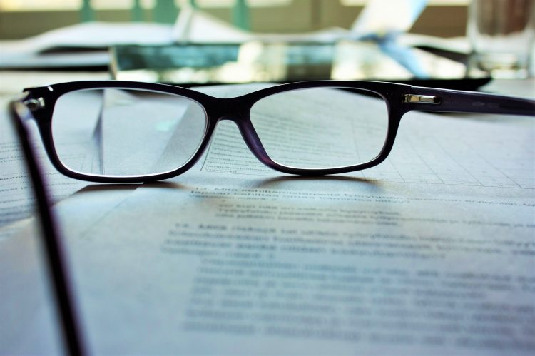 eyeglasses resting on a piece of office paper